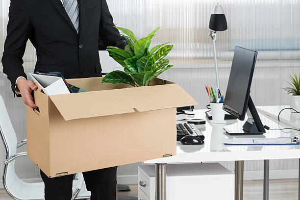Midsection of businessman carrying cardboard box by desk in office moving